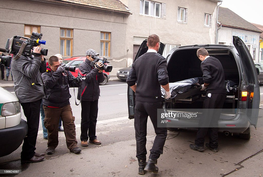 Journalists take pictures as workers of a funeral company take a body of a victim on November 22, 2012 after a former employee shot dead three former colleagues at Slovak engineering firm TC Trade in the city of Zvolen, central Slovakia. A disgruntled company executive walked into his former employer's offices in Zvolen, central Slovakia, and shot dead three ex-colleagues before being arrested, police said.