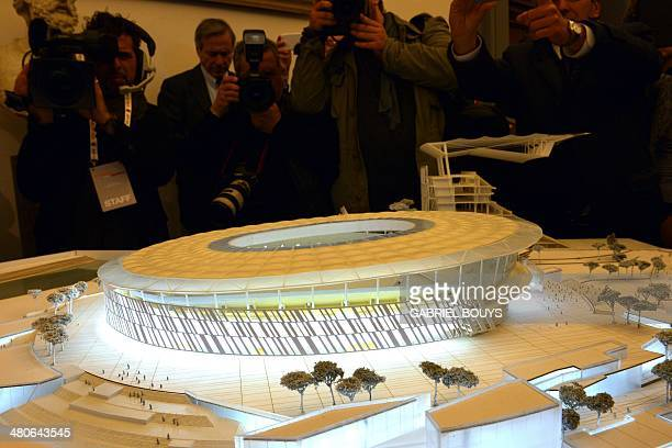 Journalists take pictures of a model presenting the Rome's new stadium project during a press conference on March 26 2014 in Rome AS Roma officially...