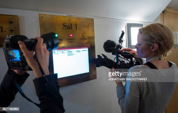 Journalists take pictures of a screen at Stockholm District Court on April 11 showing informations about remand hearings of Uzbek national Rakhmat...