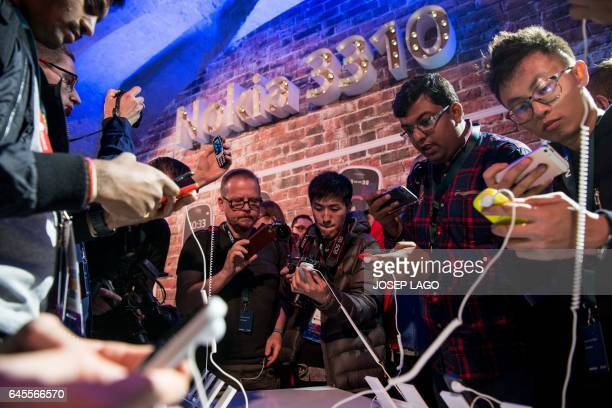 Journalists take pictures of Nokia's new phone 'Nokia 3310' after its presentation on February 26 2017 in Barcelona on the eve of the start of the...