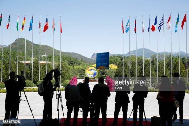 Journalists take pictures outside the venue of a summit at the Belt and Road Forum on May 15 2017 in Beijing China The Belt and Road Forum focuses on...