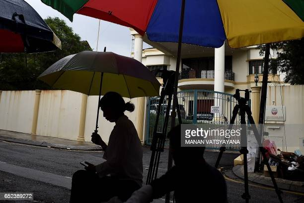 Journalists take shelter from rain outside the North Korean embassy in Kuala Lumpur on March 12 2017 Malaysia hopes to open negotiations with North...