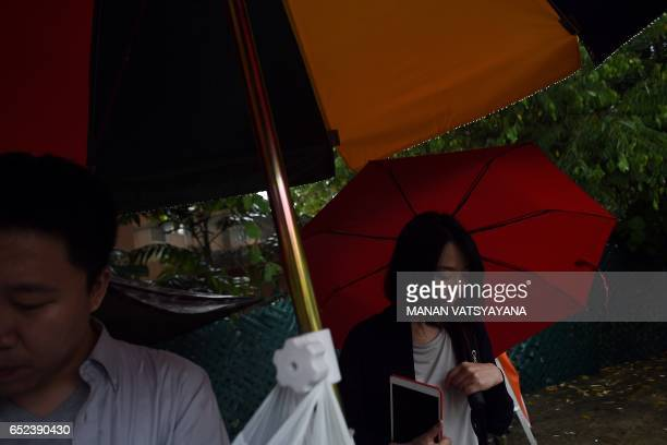 Journalists take shelter from the rain outside the North Korean embassy in Kuala Lumpur on March 12 2017 Malaysia hopes to open negotiations with...