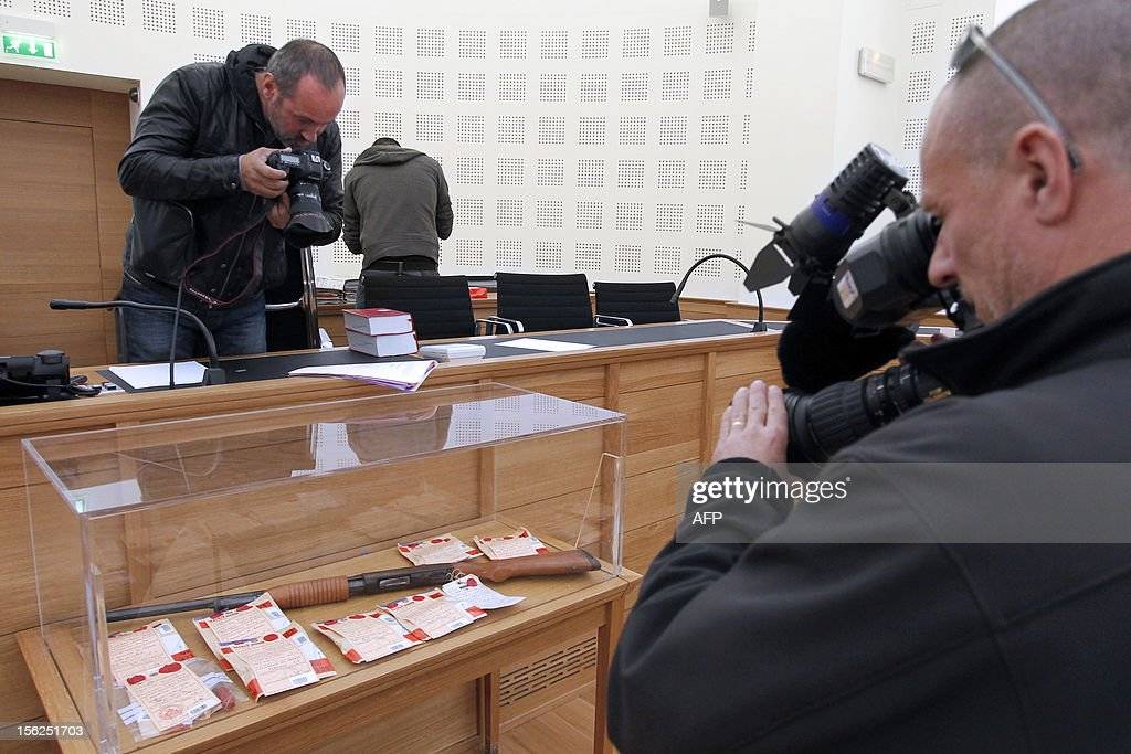 Journalists takes seals, including a rifle, in picture in a courtroom on November 12, 2012 in Ajaccio prior to the start of the trial of 19-year-old boy for shooting dead his parents and 10-year-old twin brothers in 2009. The accused, named as Andy, exterminated the entire family in August 2009 with his father's Winchester rifle in an act he said occurred in a trance-like state.