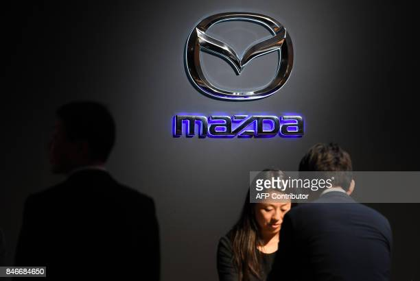 Journalists talk with a Mazda employee at the reception desk during the company's press preview of the new Mazda CX8 in Tokyo on September 14 2017...