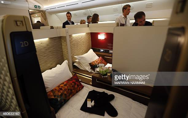 Journalists tour the first class section on the Etihad Airways Boeing B787 at Abu Dhabi airport on December 18 2014 after the Abu Dhabibased...