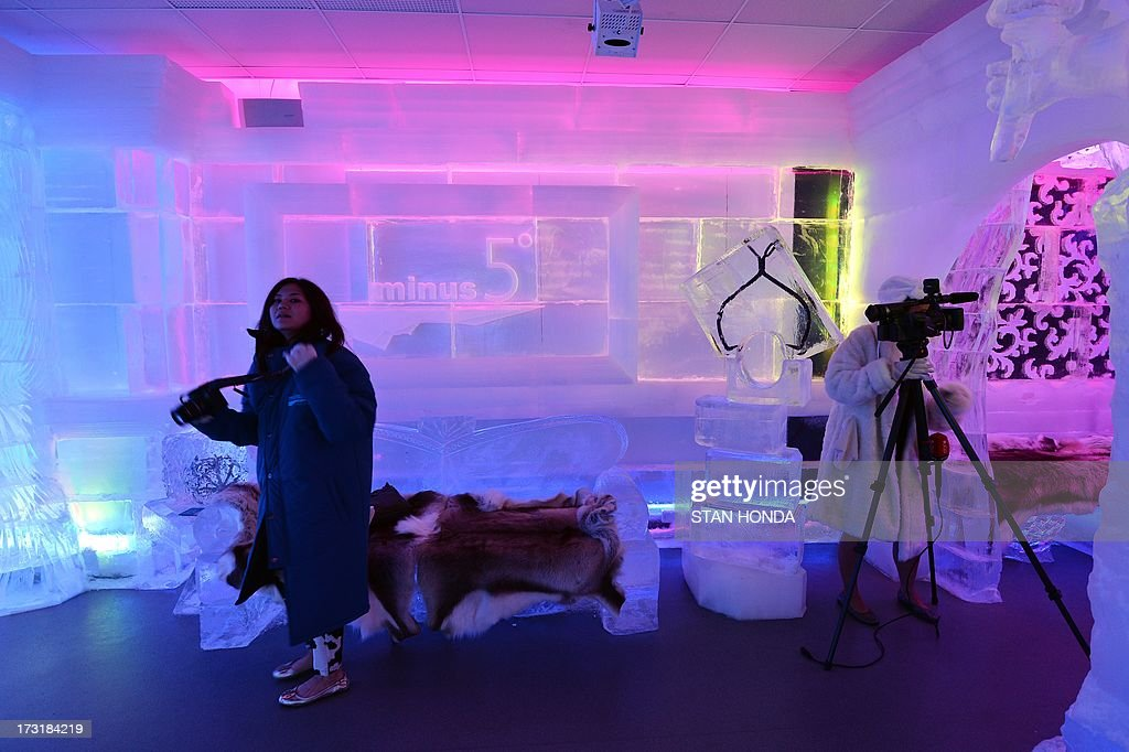 Journalists tour the Minus 5 Ice Bar during a preview at the New York Hilton Midtown Hotel July 9, 2013 in New York. The bar is constructed of 90 tons of ice and is kept at a temperature of -5 degrees C (23 degrees F). Guests are given parkas, gloves and hats and for an additional fee, fur coats. Designs in the wall and around the bar are carved by ice sculptor Peter Slavin. AFP PHOTO/Stan HONDA