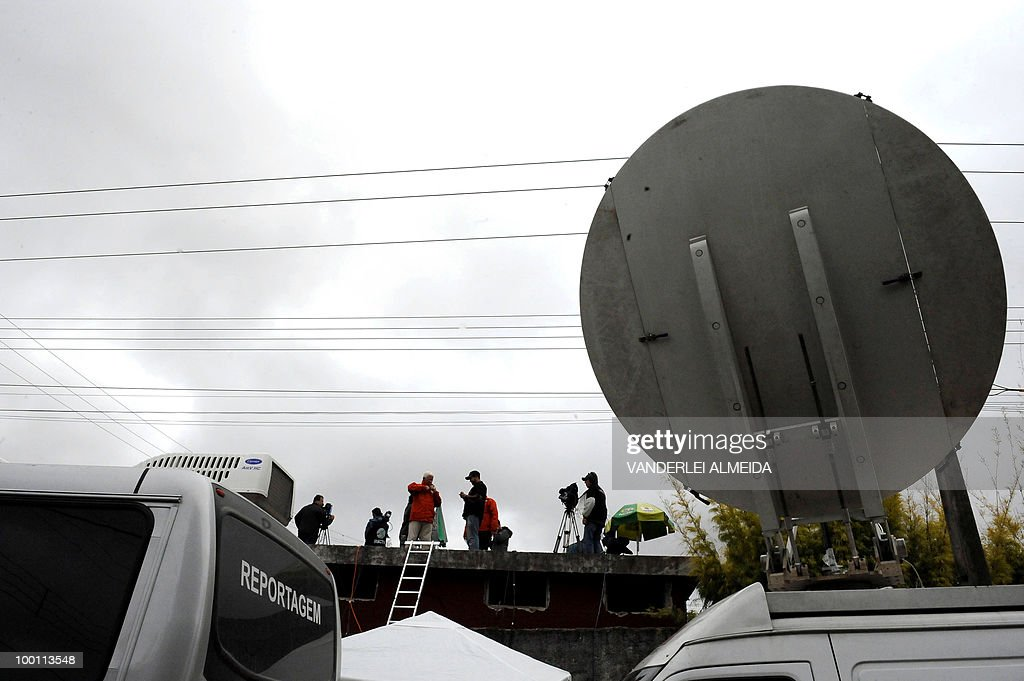 Journalists trie to look from a roof inside of the training center where the Brazilian football team gets prepared for the FIFA World Cup South Africa-2010, in Curitiva on May 21, 2010.