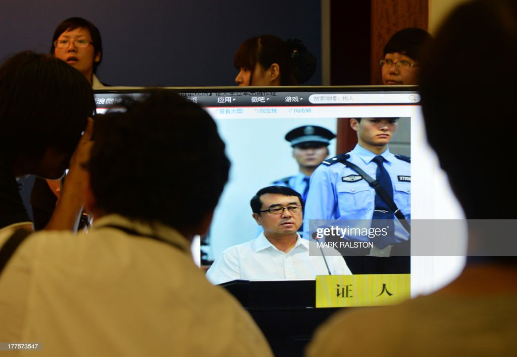 Journalists view images on a television of former police chief Wang Lijun as he gives evidence on the third day of the trial of disgraced politician Bo Xilai at the Intermediate People's Court in Jinan, Shandong Province on August 24, 2013. Once one of China's highest-flying politicians, Bo Xilai found himself in the criminal dock on trial for bribery and abuse of power in the country's highest-profile prosecution in decades. AFP PHOTO/Mark RALSTON