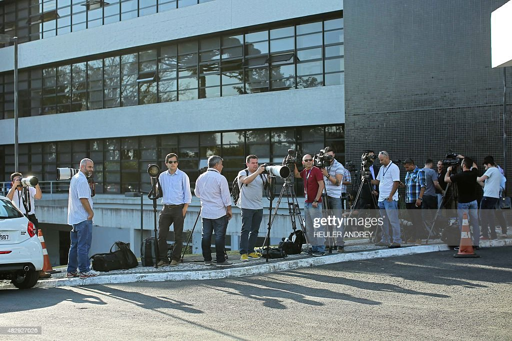 Journalists wait for Brazilian former chief of staff Jose Dirceu outside the Federal Police headquarters in Curitiba Brazil on August 4 2015...