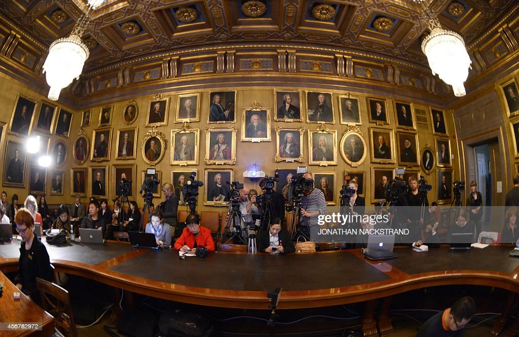 Journalists wait for the beginning of a press conference to announce the winner of the 2014 Nobel Prize in Physics on October 7 2014 at the Royal...