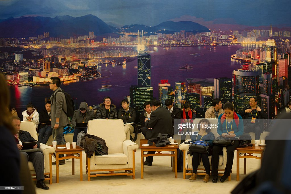 Journalists wait in a room before a backdrop of the Hong Kong skyline inside the Great Hall of the People during the closing ceremony of the Communist Party Congress in Beijing on November 14, 2012. The week-long Communist Party Congress will end with a transition of power to Vice President Xi Jinping, who will govern for the coming decade amid growing pressure for reform of the communist regime's iron-clad grip on power. AFP PHOTO / Ed Jones