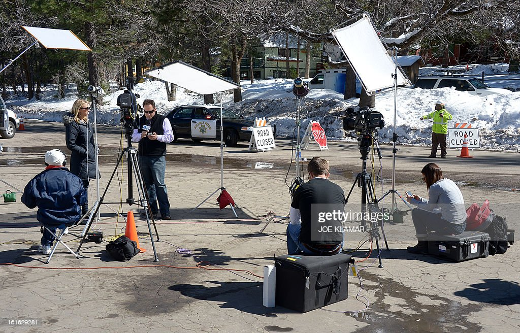 TV journalists wait near a roadblock of Highway 38 at Angelus Oaks, California, on February 13, 2013. A former US cop wanted for at least three murders is thought to have died at the scene of a shootout with police but his remains must still be identified, officials said February 13. Police discovered human remains in the charred ruins of a cabin after a fire erupted during an intense gunbattle in the snowy mountains east of Los Angeles, where fugitive Christopher Dorner was thought to have taken refuge.