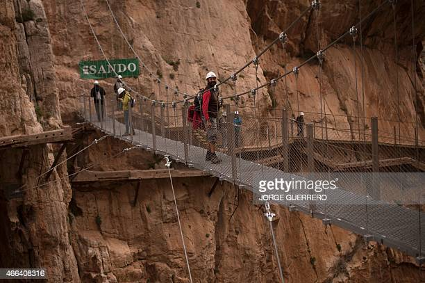 Journalists walk during a visit to the footpath 'El Caminito del Rey' a narrow walkway hanging and carved on the steep walls of a defile in Ardales...