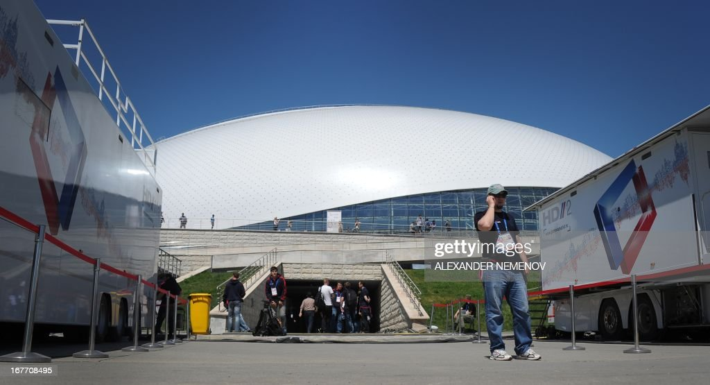 Journalists walk outside the Bolshoi Ice Dome arena - ice hockey venue at the Olympic Park in Adler outside Sochi, during the IIHF U18 International Ice Hockey World Championship on April 28, 2013.
