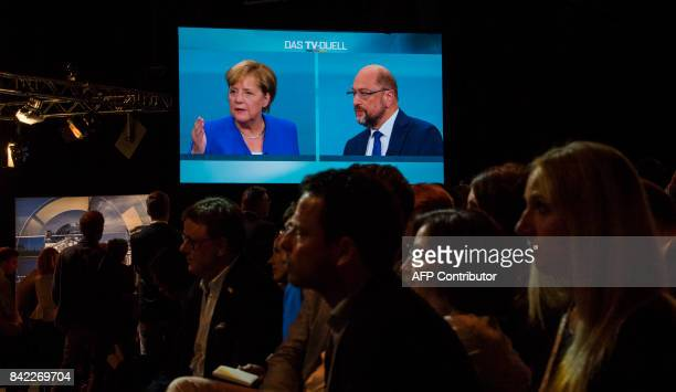 Journalists watch a televised debate between German Chancellor and leader of the conservative Christian Democratic Union party Angela Merkel and...