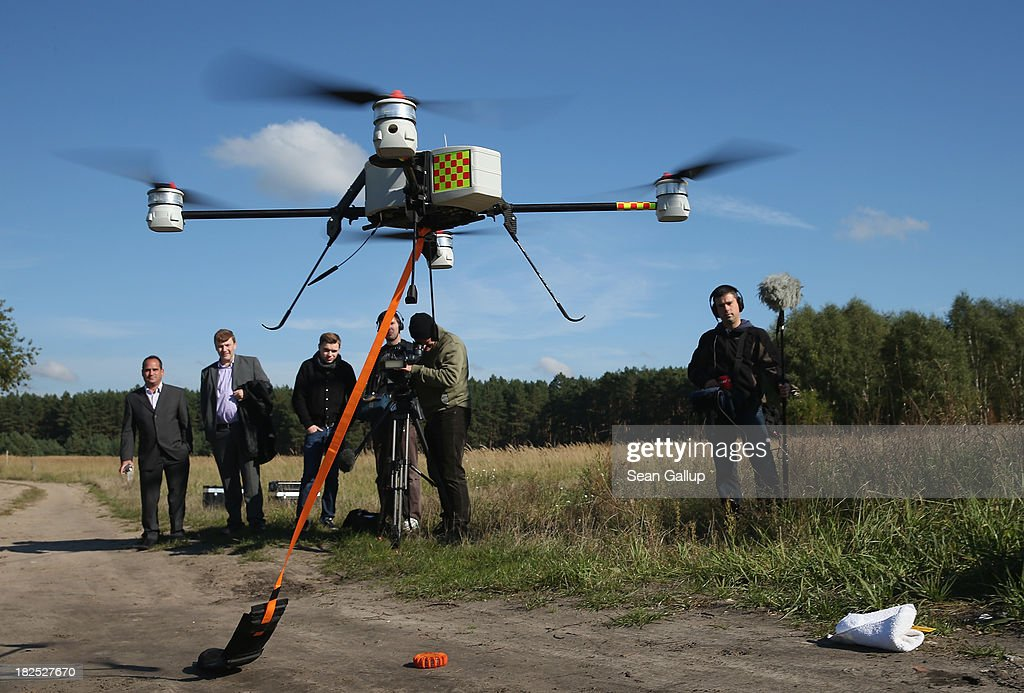 Journalists watch as a quadrocopter drone fitted with a device for marking telephone cables with artifical DNA takes off during media presentation by...