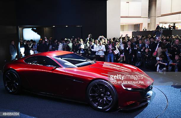 Journalists watch as Mazda's new concept rotaryengine sports car 'RXVISION' is unveiled at the Tokyo Motor Show in Tokyo on October 28 2015 AFP PHOTO...