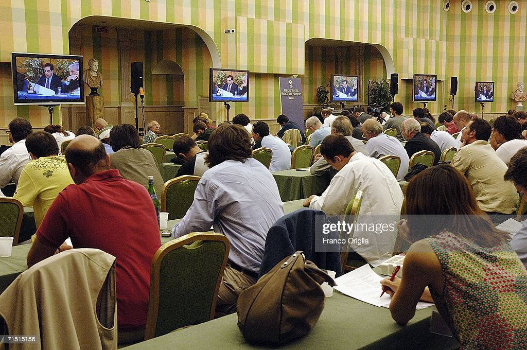 Journalists watch Italian football appeal court president Piero Sandulli on a screen as the Federal Appeals Commission deliver the definitive...