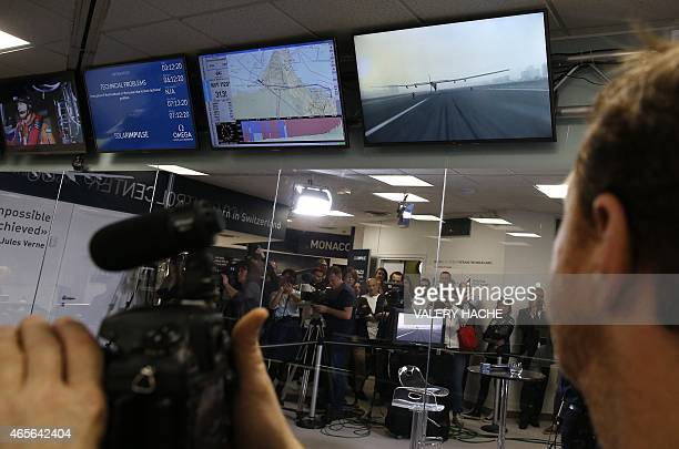 Journalists work as telemetry screens and live video feeds are pictured at the control centre for the Solar Impulse 2 solar powered aircraft in...