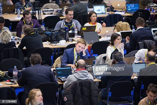 Journalists work during a European Summit at the EU Headquarters in Brussels on February 19 2016 / AFP / JOHN THYS