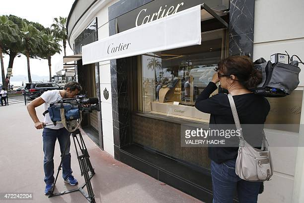 Journalists work in front of the Cartier jewellery shop on the Croisette in Cannes French Riviera on May 5 after the hold up by four armed men who...