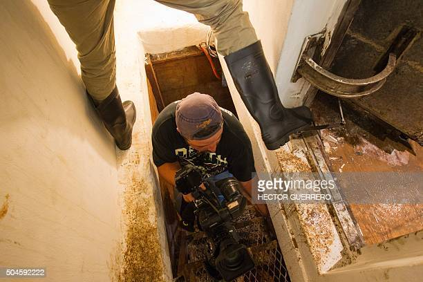 Journalists work on a tunnel through which Mexican drug kingpin Joaquin 'El Chapo' Guzman tried to escape during the military operation that resulted...