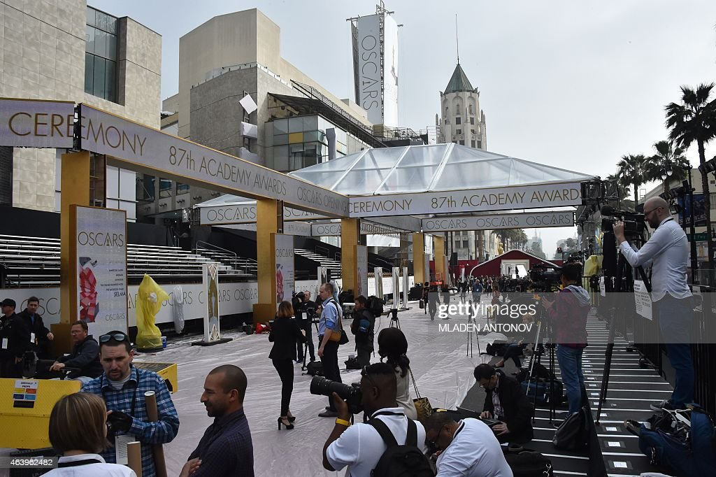 Journalists work on the red carpet area outside the Dolby Theatre as preparations are underway for the 87th annual Academy Awards in Hollywood...