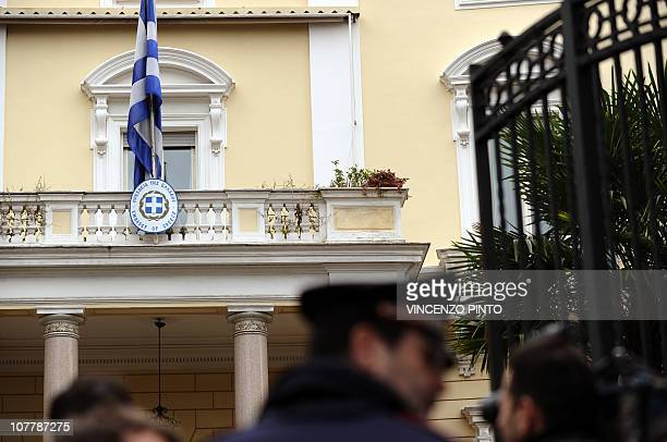 Journalits and Carabinieri stand in front of the Greek embassy on December 27 2010 in Rome after a parcel bomb was found today just days after two...