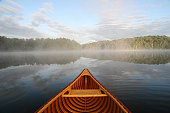 Bow of a cedar canoe being paddled on a northern Ontario lake