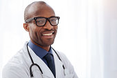 Help people. Gay afro american male doctor posing on light background while smiling and gazing at camera