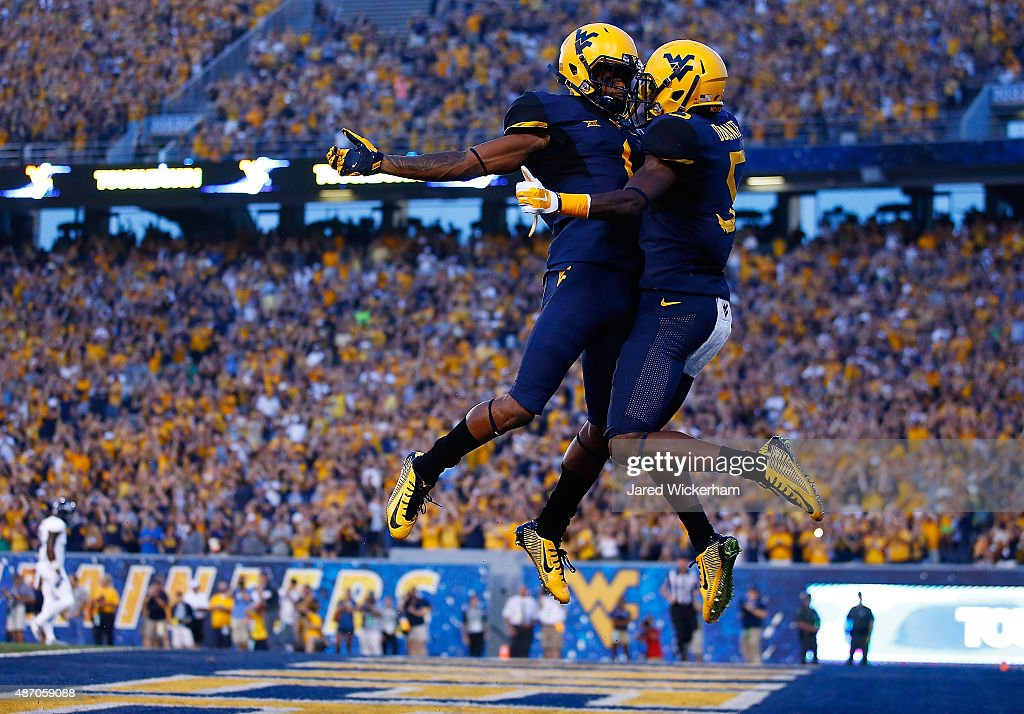 Jovon Durante of the West Virginia Mountaineers celebrates with teammate Tyrek Cole after catching a touchdown pass in the first quarter against the...