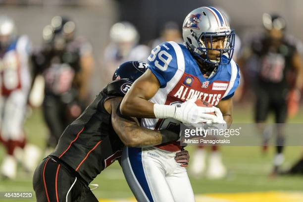 Jovon Johnson of the Ottawa Redblacks grabs a hold of Duron Carter of the Montreal Alouettes during the CFL game at Percival Molson Stadium on August...