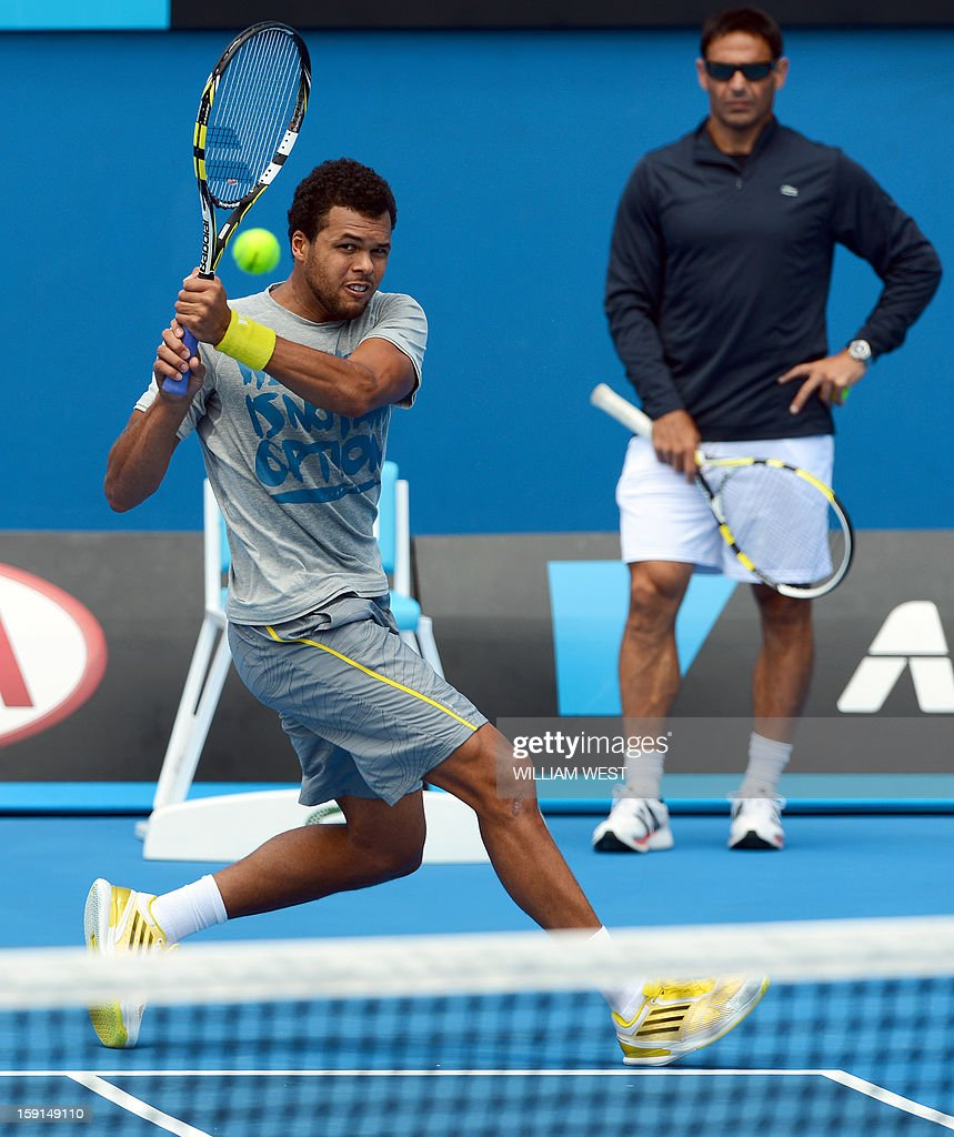 Jo-Wilfried Tsonga of France (L) hits a backhand return as coach Roger Rasheed (R) looks on during a training session at Melbourne Park on January 9, 2013. Top players are arriving in Melbourne ahead of the Australian Open which runs from January 14 to 27. AFP PHOTO/William WEST USE