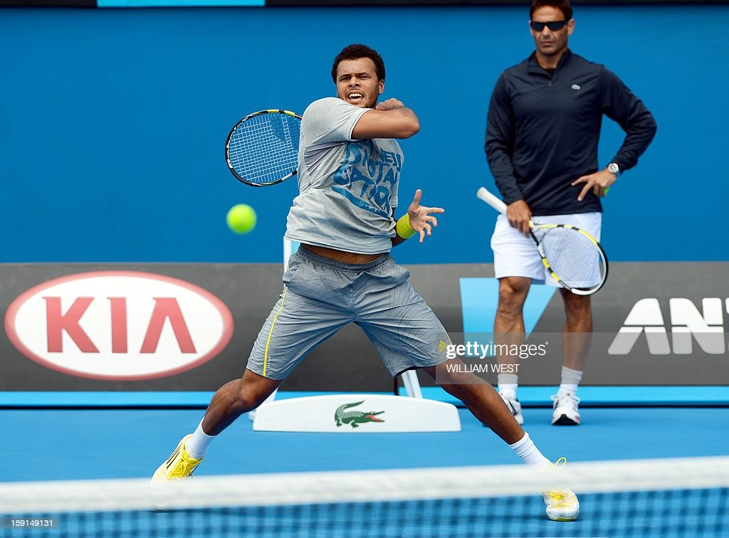 Jo-Wilfried Tsonga of France (L) hits a forehand return as coach Roger Rasheed (R) looks on during a training session at Melbourne Park on January 9, 2013. Top players are arriving in Melbourne ahead of the Australian Open which runs from January 14 to 27. AFP PHOTO/William WEST USE
