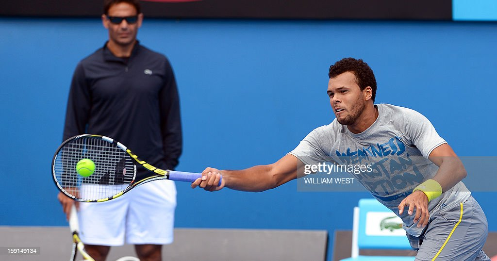 Jo-Wilfried Tsonga of France (R) hits a forehand return as coach Roger Rasheed (L) looks on during a training session at Melbourne Park on January 9, 2013. Top players are arriving in Melbourne ahead of the Australian Open which runs from January 14 to 27. AFP PHOTO/William WEST USE