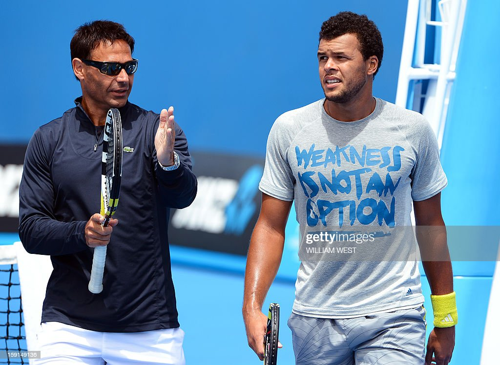 Jo-Wilfried Tsonga of France (R) listens to coach Roger Rasheed (L) during a training session at Melbourne Park on January 9, 2013. Top players are arriving in Melbourne ahead of the Australian Open which runs from January 14 to 27. AFP PHOTO/William WEST USE