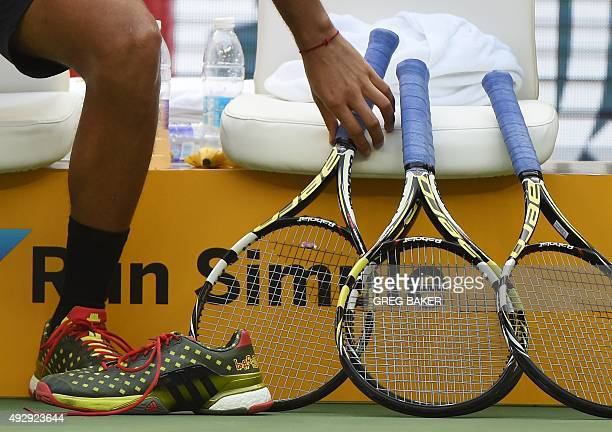 JoWilfried Tsonga of France picks up a racquet during his men's singles quarterfinal match against Kevin Anderson of South Africa at the Shanghai...