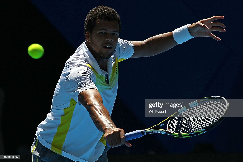Jo-Wilfried Tsonga of France plays a backhand in his singles match against Kevin Anderson of South Africa during day seven of the Hopman Cup at Perth Arena on January 4, 2013 in Perth, Australia.