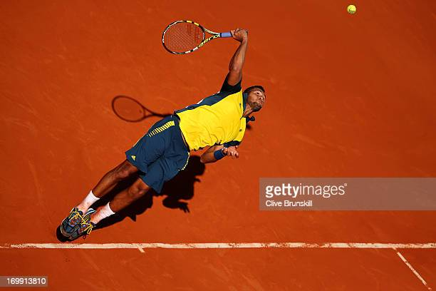 JoWilfried Tsonga of France serves in his Men's Singles quarter final match against Roger Federer of Switzerland during day ten of the French Open at...