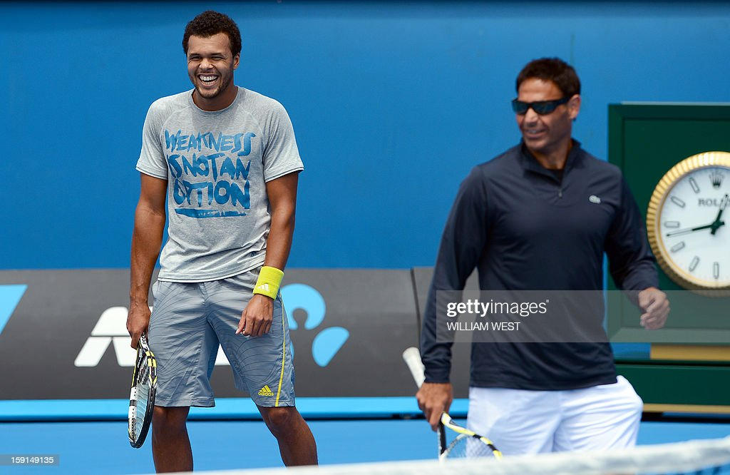 Jo-Wilfried Tsonga of France (L) shares a lighter moment with coach Roger Rasheed (R) during a training session at Melbourne Park on January 9, 2013. Top players are arriving in Melbourne ahead of the Australian Open which runs from January 14 to 27. AFP PHOTO/William WEST USE