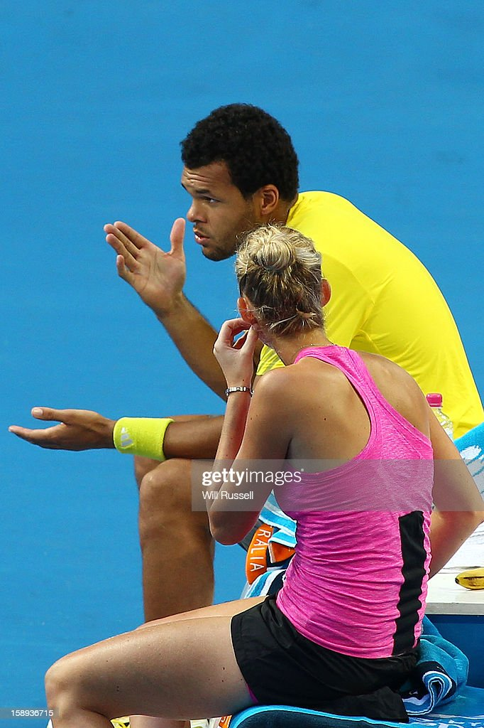 Jo-Wilfried Tsonga (L) speaks to Mathilde Johansson of France after retiring due to a leg injury sustained during their mixed doubles game against Kevin Anderson and Chanelle Scheepers of South Africa during day seven of the Hopman Cup at Perth Arena on January 4, 2013 in Perth, Australia.