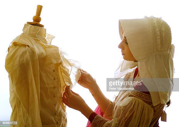Joy Asfar from Bonham's wears a beige silk dress from the 1820's as she looks at a man's outfit comprising a white shirt fine linen double breasted...
