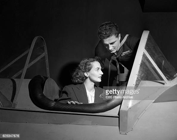 Joy Hathaway who plays the title role in the CBS Radio soap opera program Amanda of Honeymoon Hill inspects a fighter plane at a US Navy exhibit In...