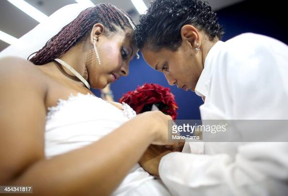 Joyce and Gabrieli make an adjustment before marrying at what was billed as the world's largest communal gay wedding on December 8 2013 in Rio de...