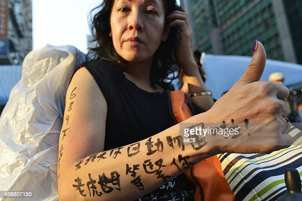 Joyce Ho who says she has been a supporter of Hong Kong protesters for three days straight shows off a 'tattoo' that in Chinese urges Hong Kong Chief...