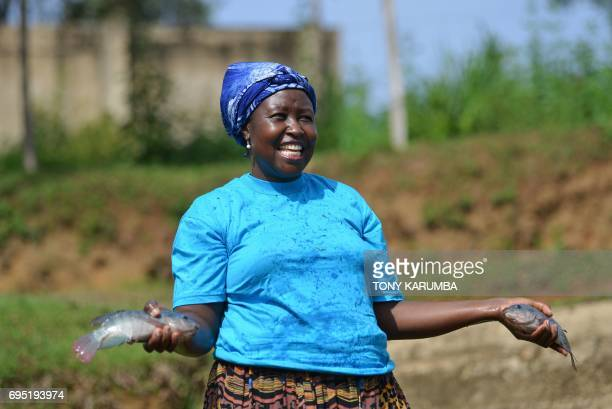 Joyce Makaka laughs with employees as she returns tilapias to an enclosure at her Jafi Enterprise fish's farm on April 24 in Lurambi Kakamega County...