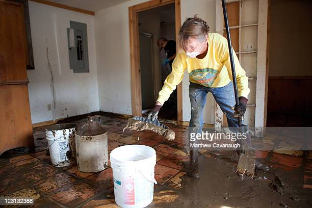 Joyce Roy cleans up mud from flooding caused by tropical storm Irene in an apartment on West Main Street on August 31 2011 in Wilmington Vermont The...