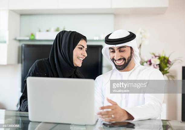 Joyful Arab Couple Spending Time at Home Using Devices