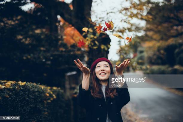 Joyful Asian girl enjoying the Autumn season with maple leaves